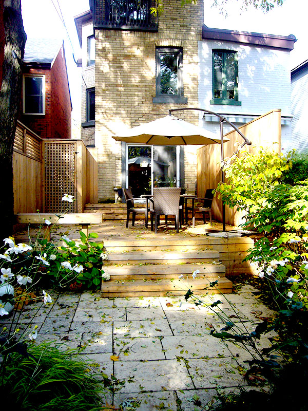 Stone patio in foreground with wood deck in background