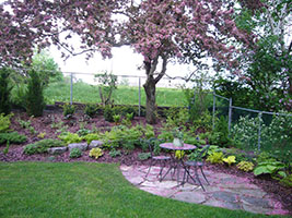 small paved patio in front of a shrub border and a pink crabapple in bloom